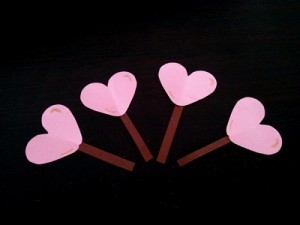 Attach the sticks to the back of the hearts.